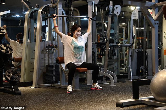 A woman wearing a mask works out at Chungwoon Sporex gym as fitness centres were allowed to re-open with appropriate hygiene measures