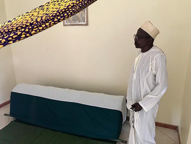 Mercy's father, Abdu Balingilira Nakendo, stands by her coffin at her funeral yesterday
