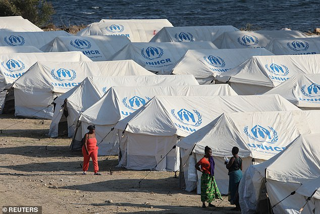 Refugees and migrants from the destroyed Moria camp are seen inside a new temporary camp, on the island of Lesbos on Monday