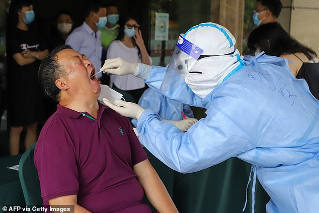 Ruili, a city with over 200,000 residents in south-western Chinese province Yunnan, Monday reported the new COVID-19 infections, two Myanmar nationals who were said to have illegally crossed the land border. A resident is pictured being tested for the virus in Ruili on Tuesday