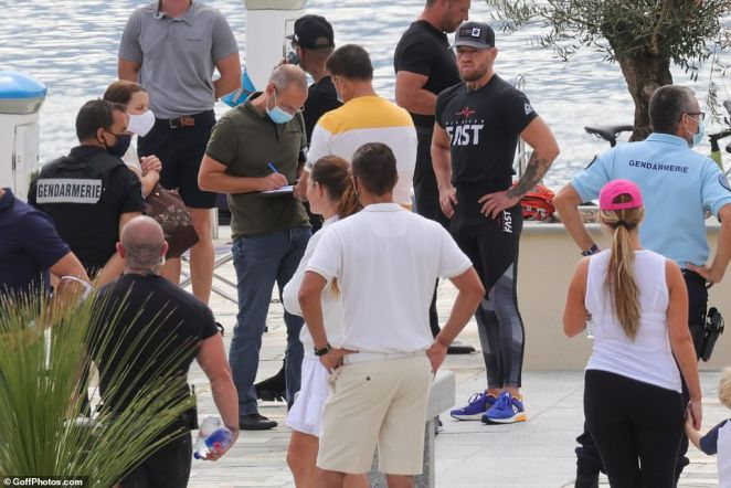 French gendarmes appeared on a quay to arrest Conor McGregor (at the right wearing a baseball cap) on the French island of Corsica over an alleged sexual assault attempt