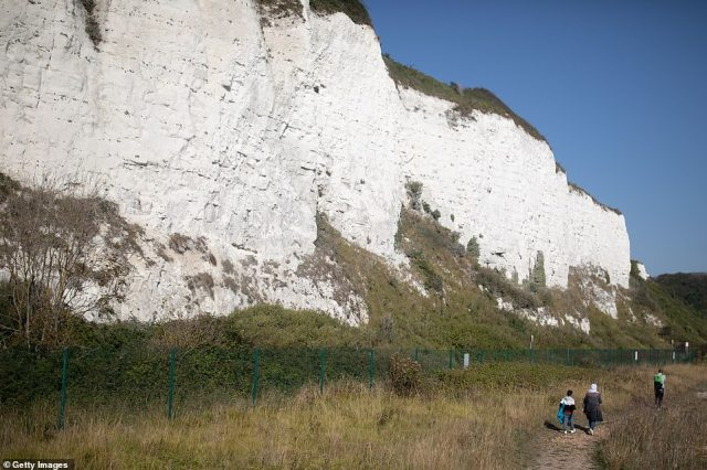 The young family walk the path below the White Cliffs of Dover today, along with other migrants who made Channel crossings