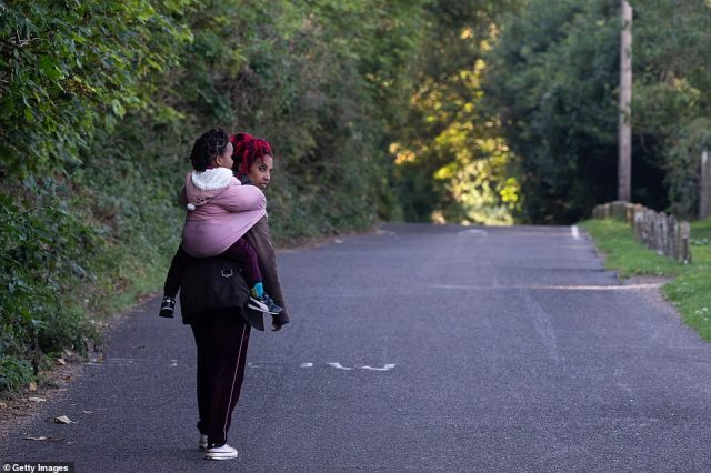 A young woman carrying a small girl walks along a country lane by the beach before being intercepted by police