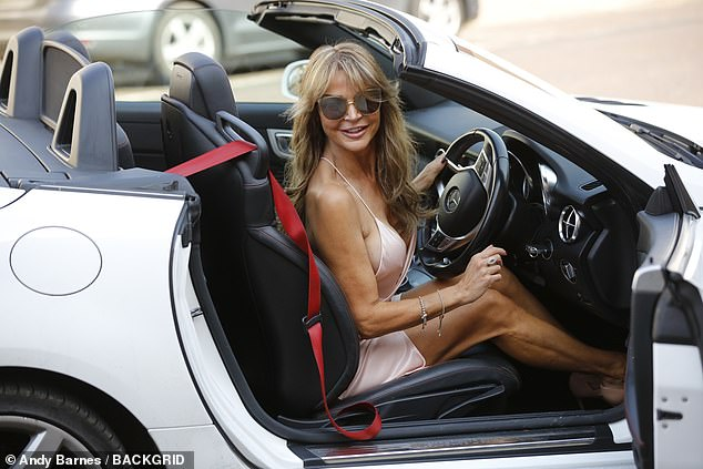 Out for a spin: Lizzie flashed a beaming smile as she drove around town in her flashy car
