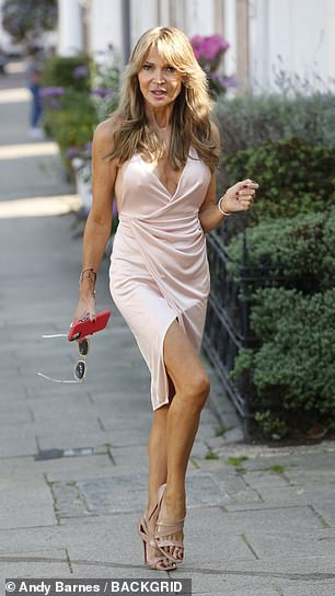 Turning heads: The former WAG's ensemble drew attention to her cleavage and lean legs, which she topped up in the sun