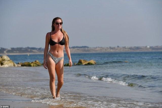 Laura Westgott, 25, cools down in the sea. Beach goers enjoy the warm temperatures at the exclusive Mudeford Sandbank beach in Dorset