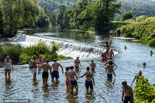 The rules came in as temperatures of up to 30C swept the country, with Britons flocking in groups to beaches and parks (above, people in the river Avon near Bath in Somerset)