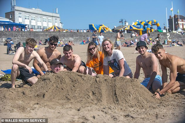 Groups of up to 30 can still gather outdoors in Wales (pictured, Cardiff university students at Barry island beach on Monday) as long as they maintain social distancing