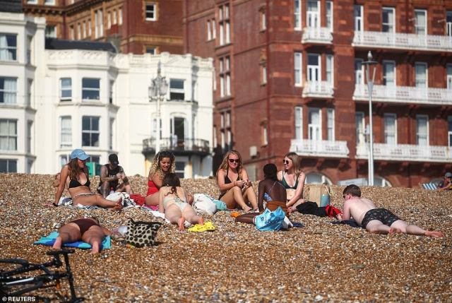 Britons have snubbed the new Covid curb on groups gatherings to enjoy the 86F sun as an Indian Summer grips the UK with unseasonal highs to last into next week. Pictured: Groups of friends enjoying the hot weather at Brighton beach