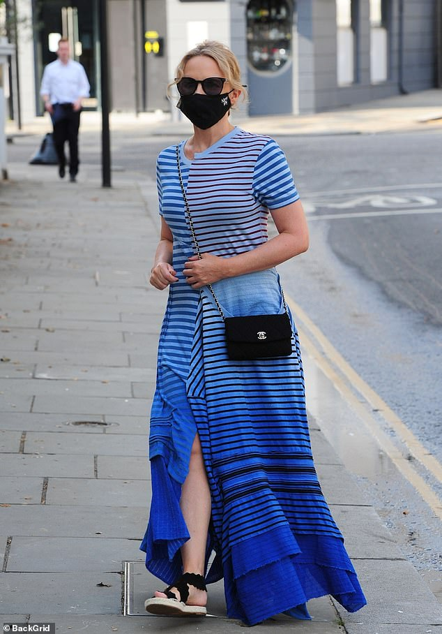 Stunner: Kylie Minogue made a style statement in blue striped maxi dress with a split and a designer face mask on an outing in London on Tuesday