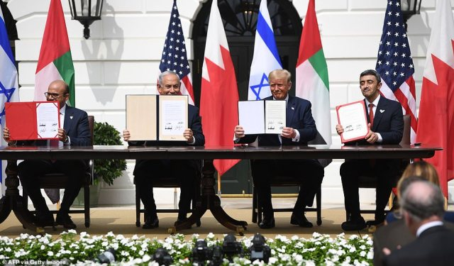 The four leaders hold up the signed copies of the Abraham Accords - they signed one in English, one in Hebrew and two in Arabic