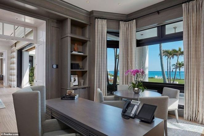 A home office boasts spectacular views out of the yard towards the private beach
