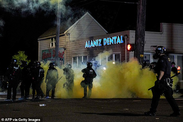 Barr claimed Democrats are pushing the idea that there will be no end to violence unless Biden wins. Pictured,Oregon police wearing anti-riot gear march towards protesters on September 5