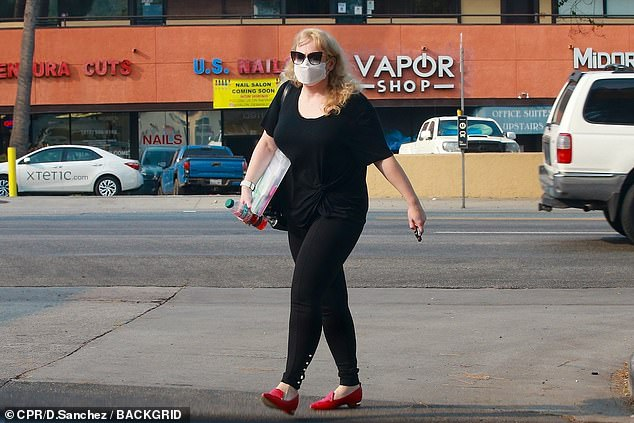 Running errands: She also carried with her a folder filled with documents, and a bottle of with a red protein water drink