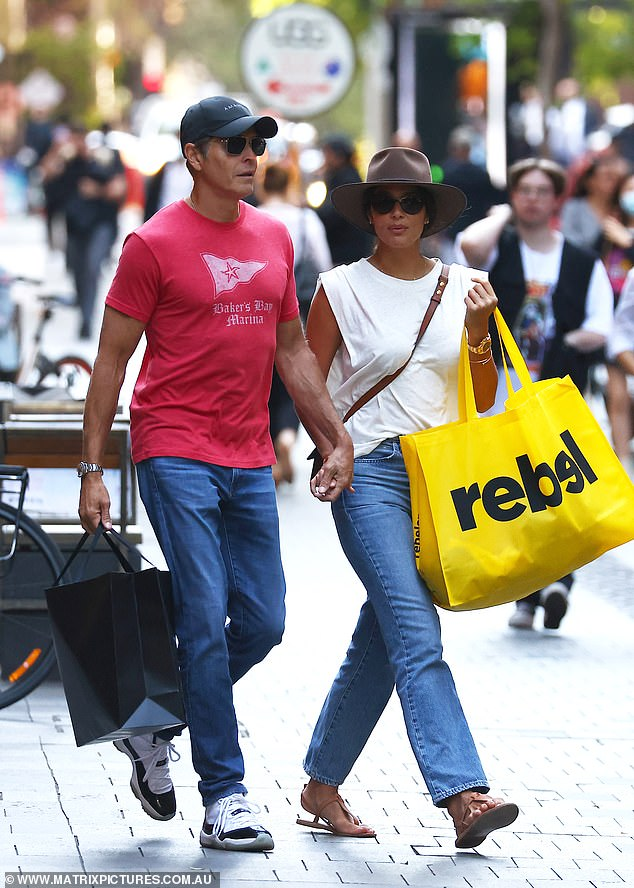 Shopping trip: The couple held bags as they visited retailers while walking along the streets in Sydney's CBD