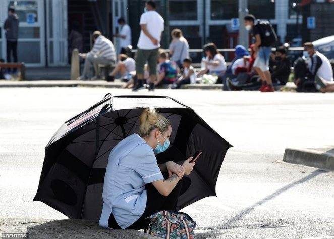 A woman uses an umbrella to shelter from the sun as she waits for a coronavirus test outside a community centre in Bury
