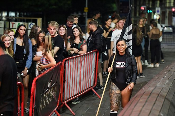 A group of party-goers flout social distancing guidelines as they queue outside a nightclub in Guidhall Walk in the coastal city of Portsmouth