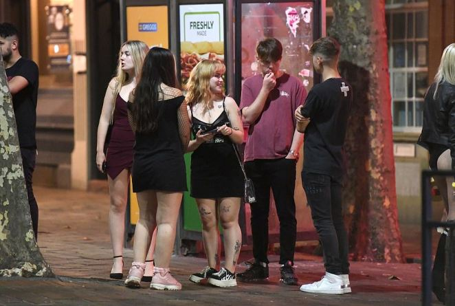 Young party-goers huddle in a group without face masks as they enjoy a night of heavy partying in Portsmouth on Tuesday