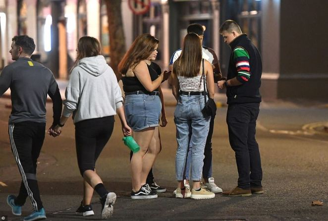A group of people flout social distancing measures as hundreds of students begin to arrive to the city to begin the academic year