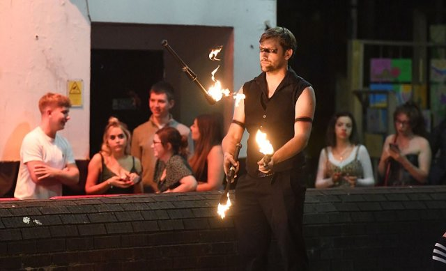 A man throws flames into the air as revellers begin to queue outside a nightclub and enjoy a night out in the city