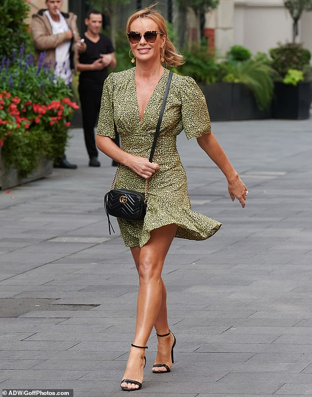 A vision of beauty: The broadcaster, 49, looked chic in a green leopard print Topshop dress with a plunging neckline and skater hem as she strutted through Leicester Square