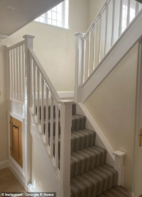 Pictured: Their current hallway with a traditional white banister and a grey-carpeted staircase