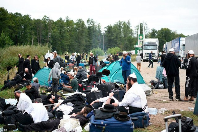 Jewish pilgrims sit on the Belarus-Ukraine border, in Belarus, Tuesday, Sept. 15, 2020. About 700 Jewish pilgrims are stuck on Belarus' border due to coroavirus restrictions that bar them from entering Ukraine. Thousands of pilgrims visit the city each September for Rosh Hashana, the Jewish new year