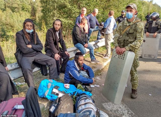 Jewish pilgrims, who plan to enter Ukraine for a pilgrimage from the territory of Belarus, gather in front of Ukrainian service members near Novi Yarylovychi crossing point in Chernihiv Region