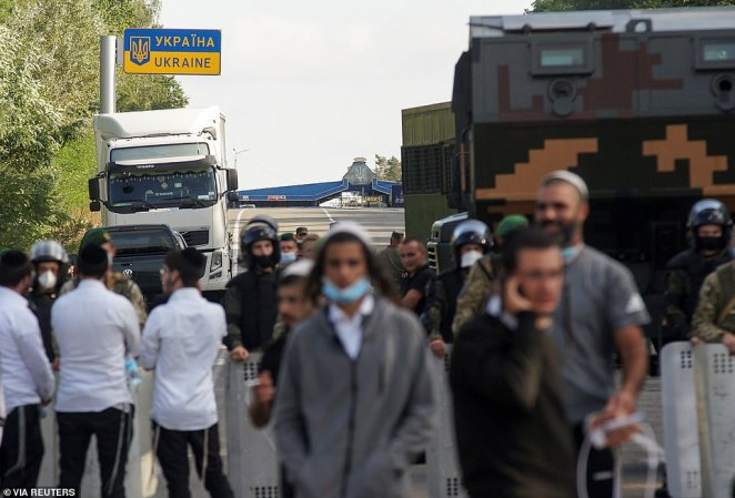 Jewish pilgrims, who plan to enter Ukraine for a pilgrimage from the territory of Belarus, gather in front of Ukrainian service members near Novi Yarylovychi crossing point in Chernihiv Region, Ukraine September 15