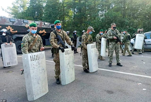 Ukrainian border guards block the road on the Belarus-Ukraine border, in Belarus, Tuesday