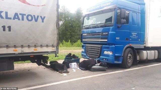 Jewish pilgrims, who plan to enter Ukraine from the territory of Belarus, rest between trucks near Novi Yarylovychi crossing point in Chernihiv Region, Ukraine