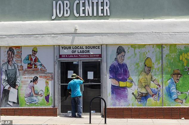 A person looks inside the closed doors of the Pasadena Community Job Center during the coronavirus pandemic in Pasadena, California in May. New federal data shows that the unemployment gap between black and white workers widened in August