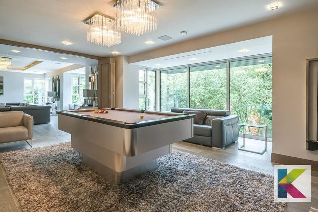 A pool table sits in one of the many open-plan lounging areas as floor-to-ceiling windows allow natural light to flood in