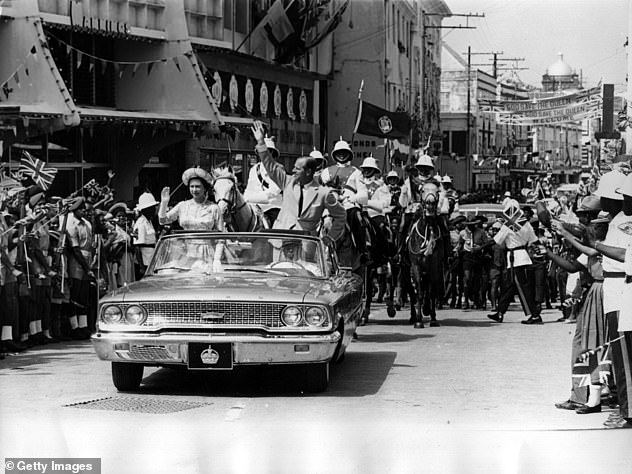 Memories: The Queen and Prince Philip are pictured driving through Barbados while waving to the crowds in February 1966