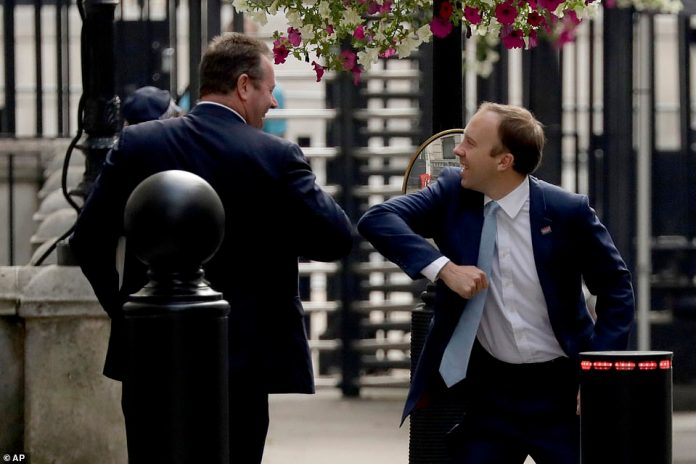 British Health Secretary Matt Hancock, right, and Chief Whip Mark Spencer give each other an elbow bump greeting in Downing Street in London