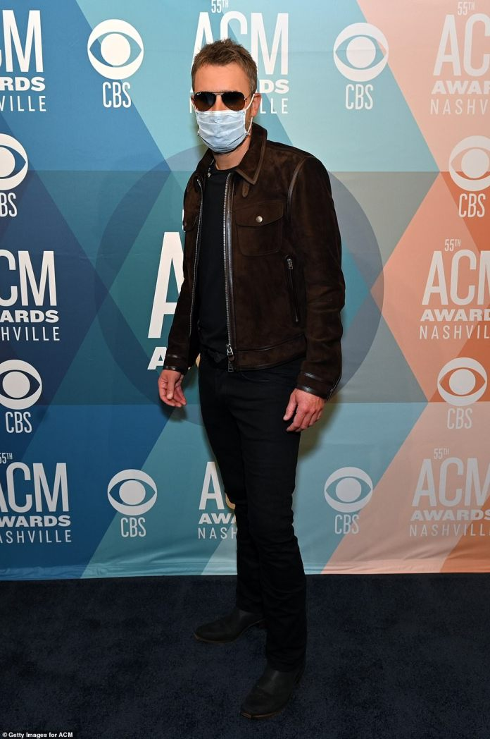 Stayed safe: Eric Church, 43, kept his face mask on as he posed for photos wearing a black shirt, pants and shoes with a chocolate brown jacket and sunglasses