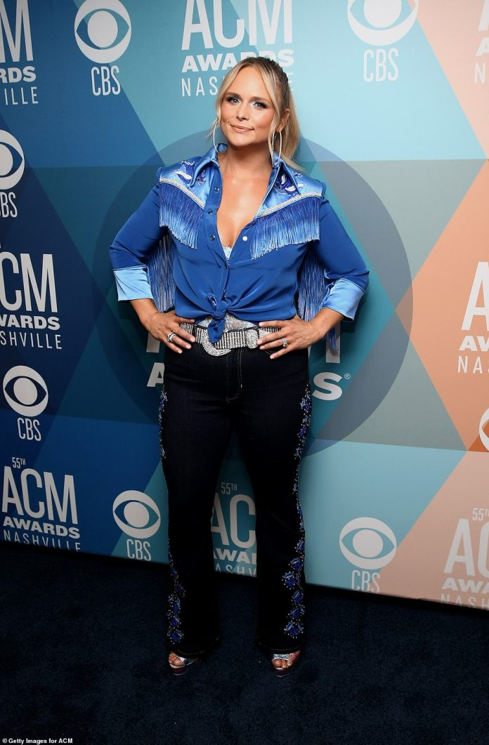 Nice look: Miranda Lambert decided to keep the country going with a blue fringed shirt and black pants embroidered with blue patterns, adding a red carpet touch with silver heels