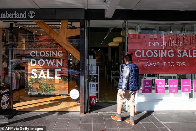 A shopper makes his way into a store offering a closing down sale in Auckland, New Zealand