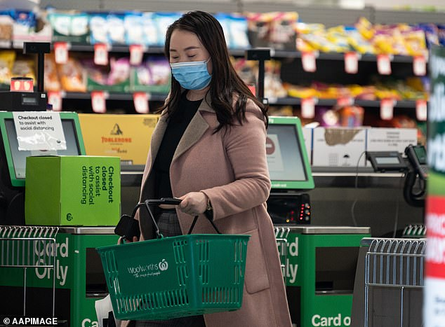 3D cameras will be set up at the entrance and exit of each store and will alert staff when too many shoppers are inside (shopper wears a face mask in a Sydney Woolworths)