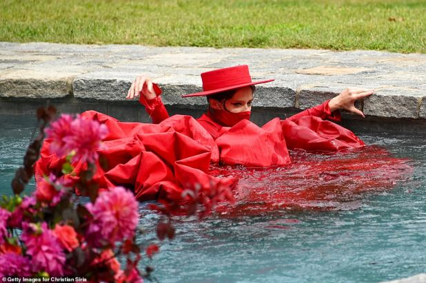 She in: Soon her wide red hat with her head popped above the hat as material from her dress floated around her