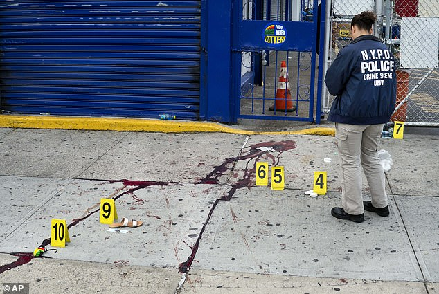 New York City's murder rate has soared by 27 percent and gang violence rocketed by more than 50 percent in 2020. Pictured NYPD cops at a crime scene on September 5 where people were killed in a shooting during J'ouvert festivities in Brooklyn