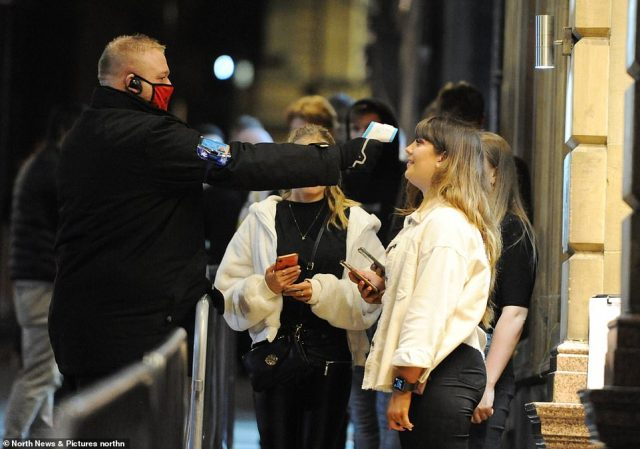 Pictured: Revellers in Newcastle have their temperatures checked before entering a club on the night before tough new measures come into place