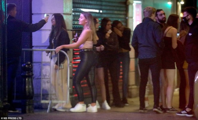 Pictured: Partygoers have their temperatures checked before entering busy clubs in the city centre on Thursday night