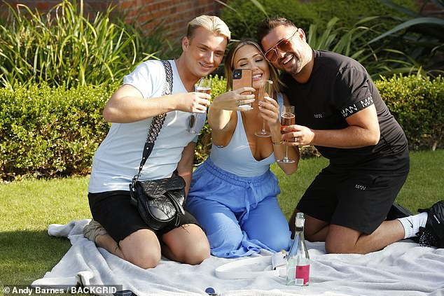 Boozy:The trio looked like they were making the most of the September sunshine as they enjoyed their drinks on a picnic blanket and took selfies