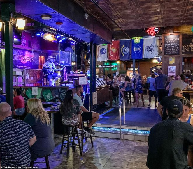 Patrons fill Irish Kevin's Bar And Restaurant in Key West during the coronavirus pandemic as the band plays behind a plastic shield