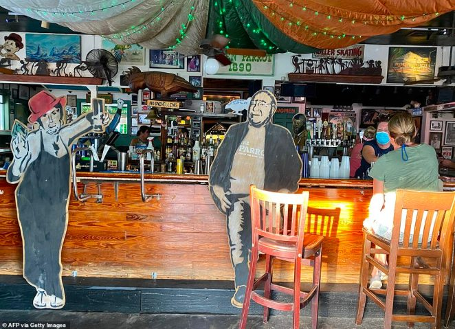 Cardboard cutouts of people are placed by the counter of a bar, helping people to respect social distancing in Key West, Florida on September 17, 2020 amid the coronavirus pandemic