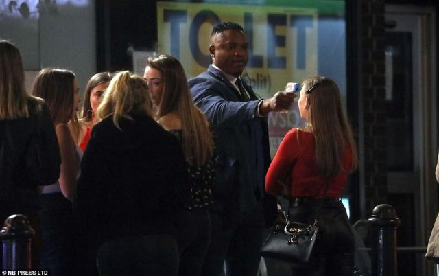 A doorman in Leeds uses a temperature reader on a patron as people queue up to head to bars in the city centre last night