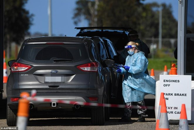 A health worker is pictured approaching a vehicle at a COVID-19 testing centre in Cranbourneon September 17