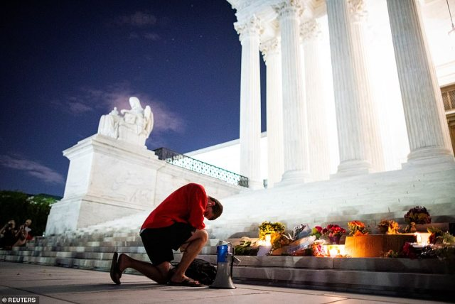 A man kneels as he brings a megaphone to a vigil on the steps of the U.S. Supreme Court following the death of U.S. Supreme Court Justice Ruth Bader Ginsburg, in Washington