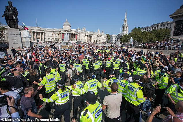During increasingly ugly scenes a Mail on Sunday photographer was surrounded by a group of screaming protesters and had his face mask ripped off